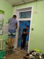 Рабочие заканчивают монтаж двери